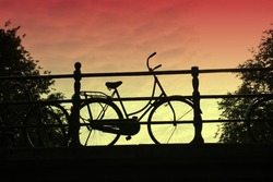 A bicycle on a bridge, silhouetted against a sunset sky.  Common mode of transport in Amsterdam, Holland.