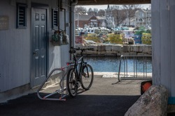 A bicycle parked under an overhang that looks out into a New England bay an a bright sunny spring day.