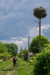 A bicyclist walks along a village street in Ukraine. Traditional stork's nest on an electric pole. Local tourism concept. Vertical image.