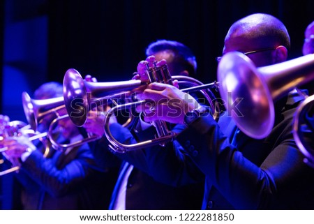 A big band trumpet section playing flugelhorns during a performance #1222281850