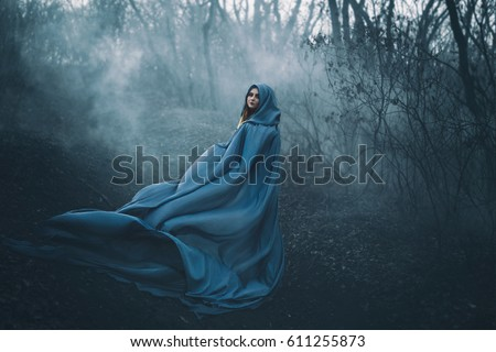 Stock Photo A big, beautiful woman in a blue raincoat, walks in a fog. Background dark forest, bare trees. Creative colors