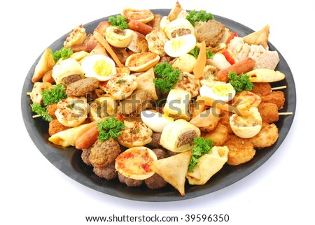A big black plate full of various meaty party snacks. Image isolated on white studio background.