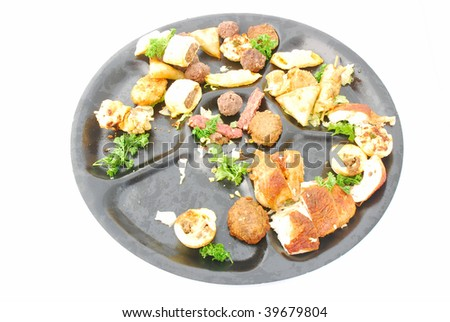 A big black plate with various food (left overs) after a party. Image isolated on white studio background.