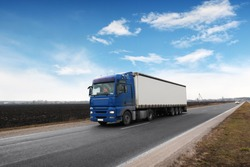 A big blue truck and a white trailer with space for text on the countryside road against a blue sky with clouds