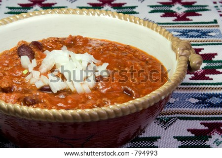 A big bowl of chili with chopped onions on top.