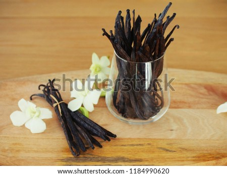 A big bunch of vanilla beans in the glass and a smaller on on the wooden board with white orchids