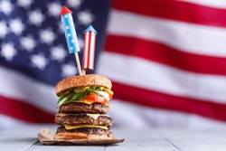 a big burger with three juicy beef patties bonded with American flag firework skewers. burgar concept for the day of independence day celebration of fourth of july