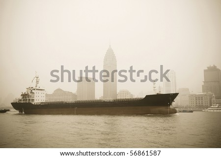 a big cargo ship sailing on huangpu river,old part of shanghai