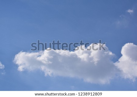 a big cloud had a shape like triangle has bright side from the light of the sun and the other side that was absorb the sun covered by shadow. Soft clouds were distributed around the sky like smoke. #1238912809