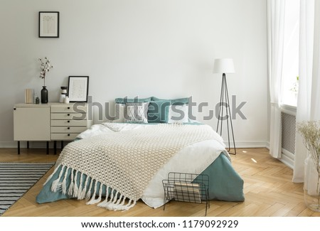 A big comfortable bed with pale sage green and white linen, pillows and blanket in a woman's bright bedroom interior with windows. Real photo.