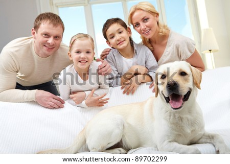 A big dog lying on sofa, a family of four standing behind