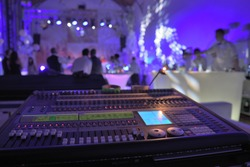 A big electronic sound mixer in the foreground of the wedding night dance music party.
