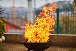A big fire flashover a black grill outdoors when having a barbecue
