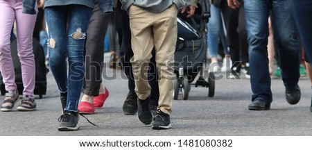 A big group of people walking to the same direction in the train station. In front, there is a young person with broken jeans and another one with brown trousers. Selective focus. Photo stock ©