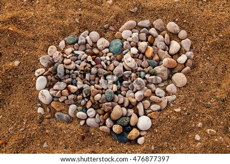 Stock Photo a big heart made of mussels. Heart of Pebbles. Hearth symbol on the sand beach on a sunny day