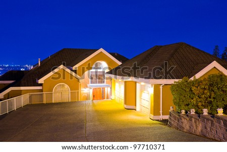 A big luxury house with double detached garage on the hills in suburbs at dusk ( night ) in Vancouver, Canada