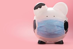 a big mom white piggy bank, wearing a surgical face mask or green doctor mask, isolated on a pink rose gold background with text space. Money saving concept in time of coronavirus pandemic crisis