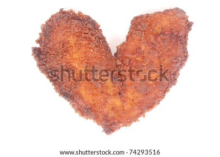 A big piece of freshly fried breaded chicken schnitzel in the shape of a heart. Image isolated on white studio background.