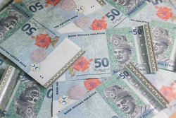A big pile of Malaysian Ringgit. A large amount of 50 ringgit banknotes. Wildly jumbled bunch banknotes of Malaysia. RM 50 unsorted on a table.  Money with red hibiscus flower and the King of Malaysia