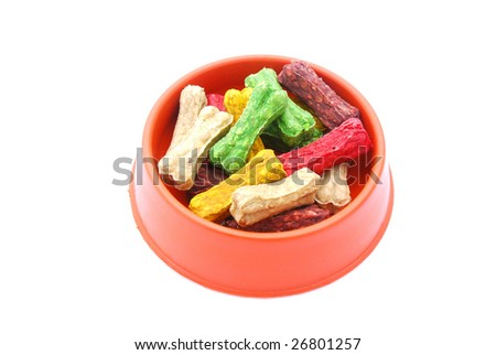A big plastic bowl of colorful little dog treat bones isolated on white studio background