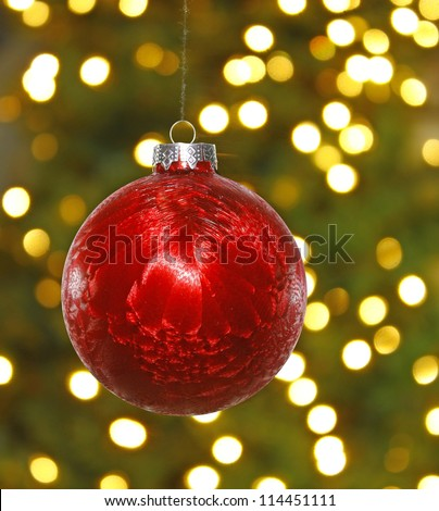 A big red hanging Christmas ball decoration in front of a blown out christmas tree background and lights