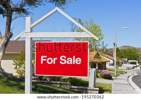 A big red sale sign hangs in the front yard of a house in a suburban community.