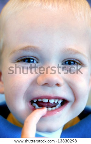A big smile from a sweet small boy with big blue eyes and blonde hair.  He has one finger in his mouth.  Blue shirt.
