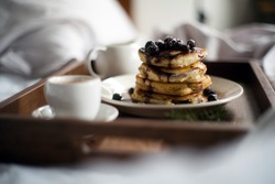 A big stack of delicious blueberry pancakes is served with syrup poured over the blueberries dripping onto the pancakes. All on a small tray ready for breakfast in bed