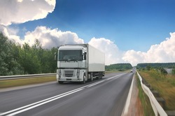 A big truck with a white trailer with space for text on a countryside road in motion against a blue sky with clouds
