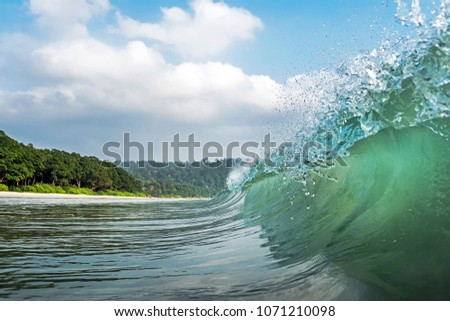 a big wave covers. Radhanagar Beach At Andaman and Nicobar Island, India. view from the sea. bursts of water at sea. The spray of water droplets. under the crest of a wave. crest of wave #1071210098