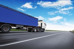 A big white truck and blue trailer with space for text on the countryside road in motion against a blue sky with clouds