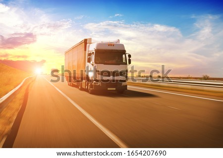 A big white truck with a red trailer and other cars on the countryside road in motion against a night sky with a sunset