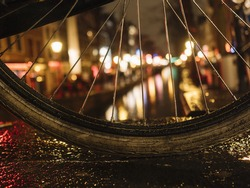 A bike rim at night on a bridge with an Amsterdam canal, lights in the background