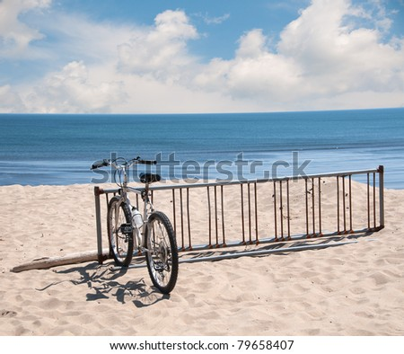 A bike sits in a bike rack on the sand dune along the Atlantic Ocean on a bright sunny summer day.