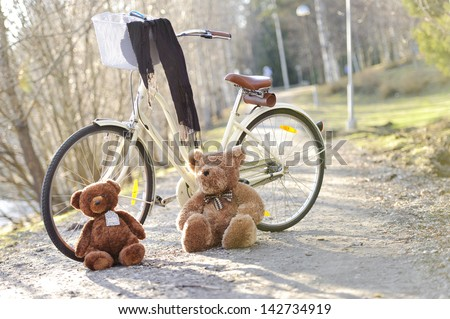 A bike standing in the park on a path in a sunny day with toys two bears light