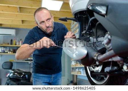 a biker fixing a motorbike