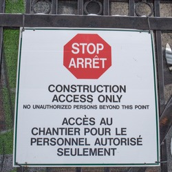 A bilingual, red and white sign on the black metal fence of a construction site reads 'Stop: Construction Access Only: No Unauthorized Personnel Beyond This Point' in English and French in Canada.