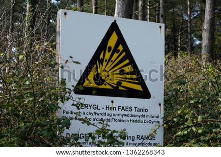 A bilingual Welsh and English sign regarding unexploded artillery on the beach at Whiteford sands on the Gower peninsula in Swansea, South Wales, UK Stock photo ©