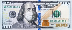 A $ 100 bill in a medical mask. World economy during the COVID-19 pandemic