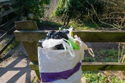 A bin filled with bags of dog poo on a walking route