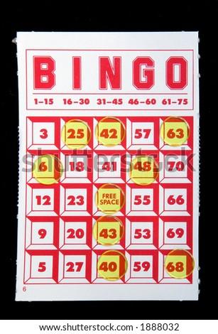 A bingo card with tokens on a black felt background..