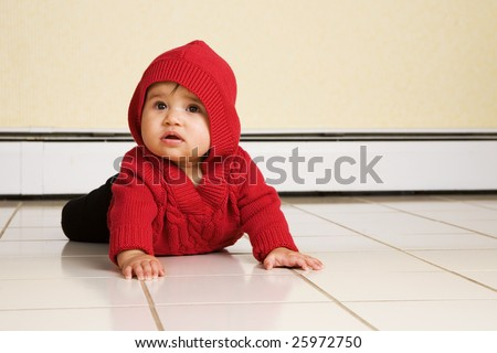 A biracial baby girl looking up as she tries to creep across a white, tile floor.