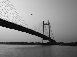 a bird flying above the Vidyasagar Setu / bridge in kolkata , India black and white from princep ghat