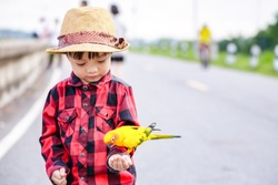 A bird on children hand in the park.