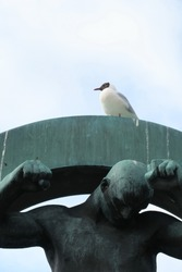 A bird perched on the head of an outdoor sculpture in Europe.