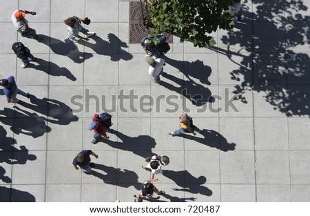 A bird's eye view of a crowd of people strolling down a sidewalk.