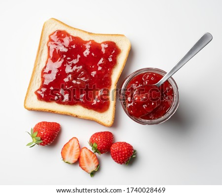 A bird's-eye view of the strawberry jam-filled bread and strawberry fruit on a white background