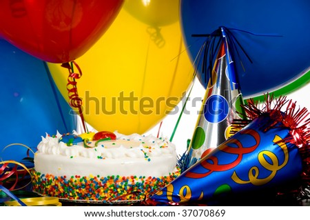 A birthday cake, colorful balloons and party hats