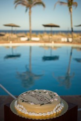 A birthday cake on the swimming pool border overlooking the sea - Lifestyle concept