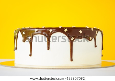 A birthday cake poured with chocolate, decorated with confectionery sprinkling stars on a yellow and white background. Picture for a menu or a confectionery catalog.